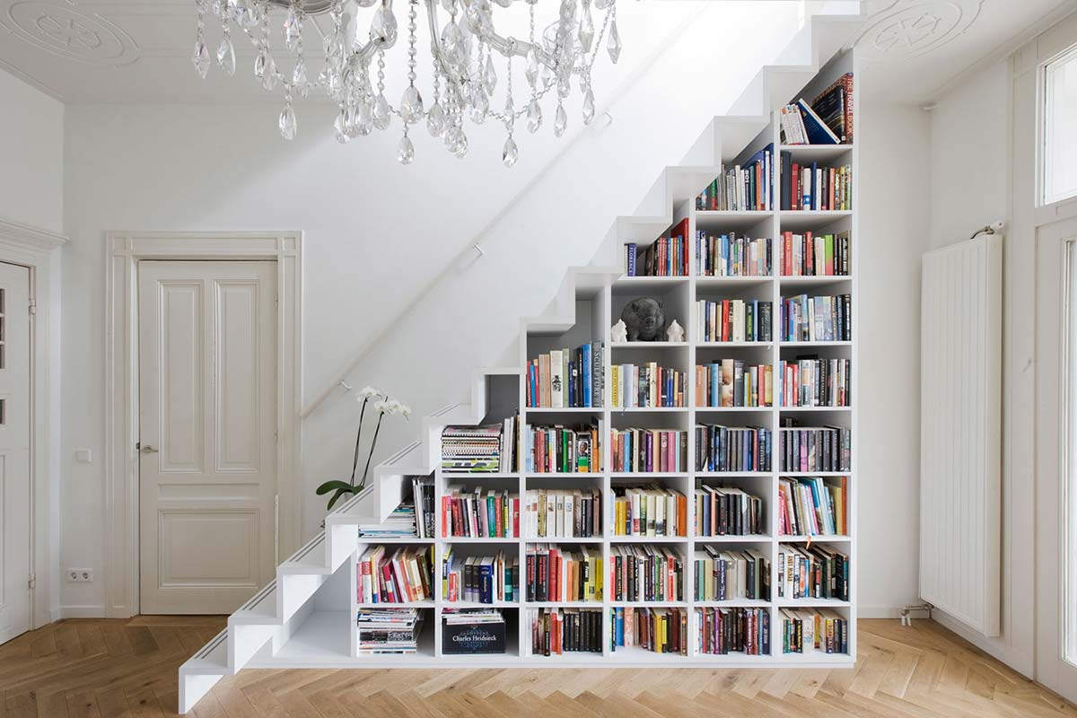 white bookcase under the stairs