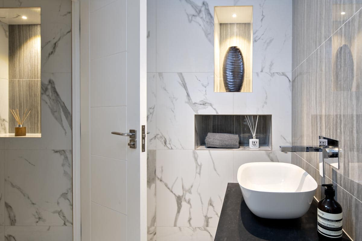 Contemporary cloakroom with porcelain marble effect tiles in Kensington
