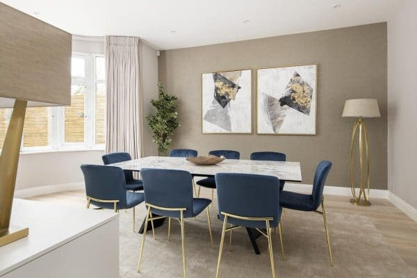 Contemporary dining room with marble table and blue and gold chairs in Kensington