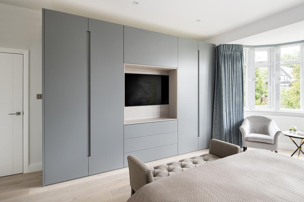 Contemporary bespoke wardrobe with TV in a blue and grey color master bedroom in Kensington